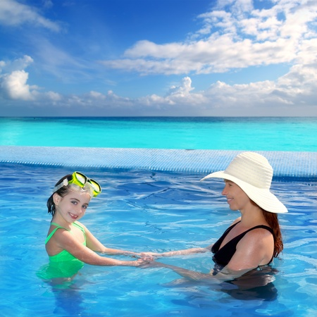 daughter and mother in swimming pool with direct view to a tropical Caribbean beach