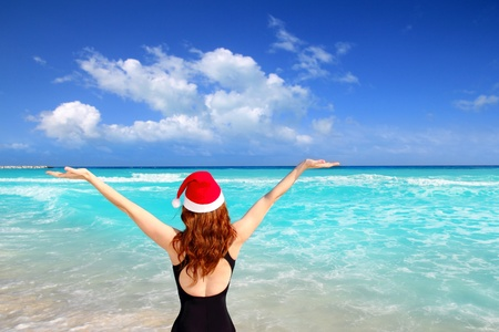 american woman christmas tourist in caribbean vacation with red santa hat photo
