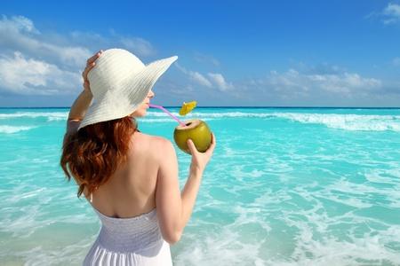 beach hat profile girl drinking acoconut fresh cocktail in tropical Caribbean sea