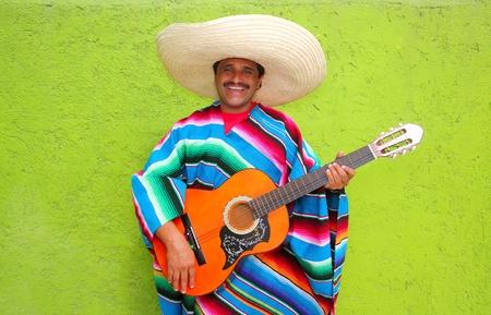 Hombre típico mexicano tocando la guitarra con poncho en pared verde
