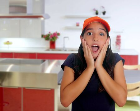 Beautiful Latin teen hispanic girl with cap and surprise gesture in a house kitchen photo