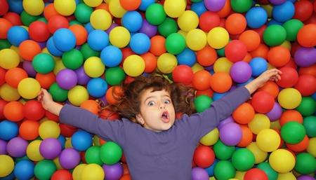 공원에서 다채로운 공을 위에 누워 재미있는 어린 소녀 행복한 몸짓