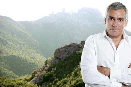 senior man portrait in green nature mountains with white shirt photo