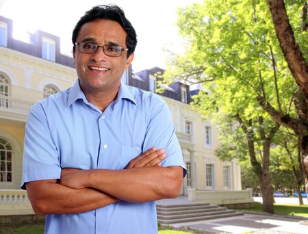 Indian latin man as hotel owner or real estate businessman smiling in front of house facade photo