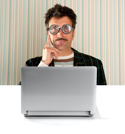 myopic: Nerd pensive man with myopic glasses and silly expression in front a laptop computer