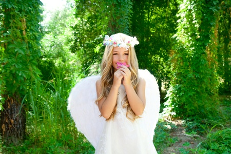 angelic: Angel children girl smelling pinks flower in forest with white wings Stock Photo