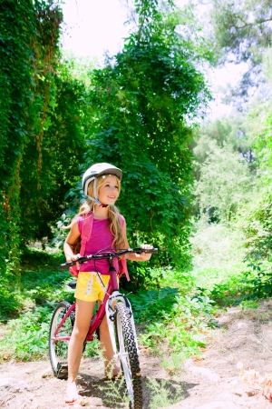 bicycle girl: Children girl riding bicycle outdoor in forest smiling with helmet