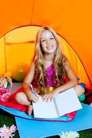 niños escribiendo: Las niñas escribir un cuaderno en tienda de campaña con las flores Foto de archivo