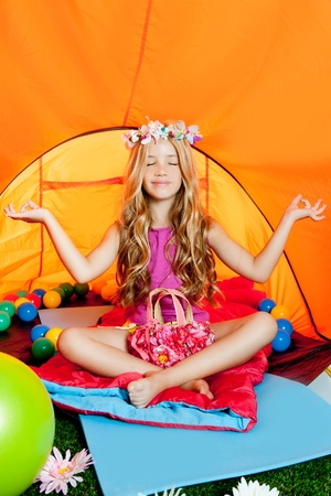 Blond little girl practicing yoga indoor of camping tent