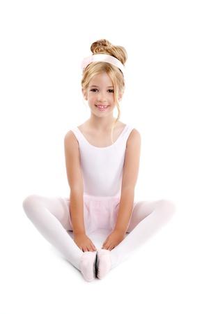 innocent girl: Ballerina children dancer sitting on white Stock Photo