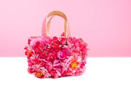 flowers spring bag in pink and red roses over white table photo