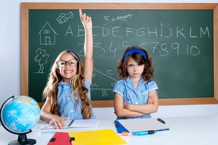 niños tristes: estudiante inteligente nerd en aula elevar la mano con triste amigo Foto de archivo