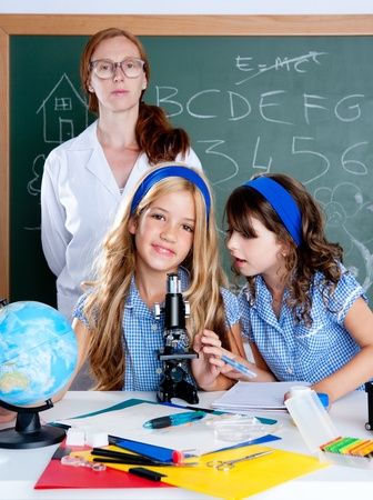 kids students with nerd teacher woman at science classroom photo