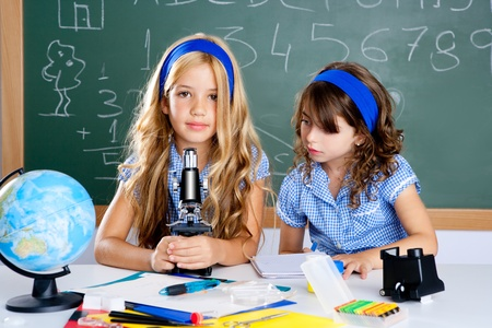 kids learning: children girls at school classroom with world map and microscope