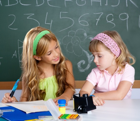 kids students in classroom helping each other at school desk photo