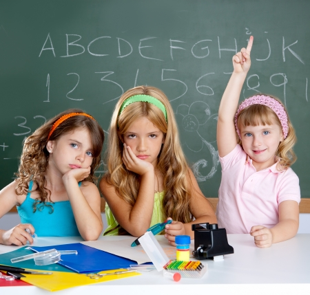 answer: bored students with smart little girl raising hand finger at school