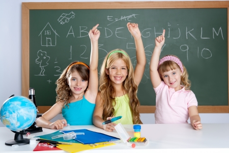 to raise: smart group of student kids at school classroom raising hand Stock Photo