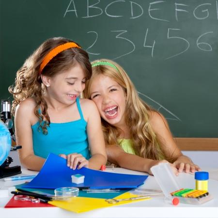 niños en la escuela: niños de estudiante riendo feliz al aula de escuela en escritorio Foto de archivo