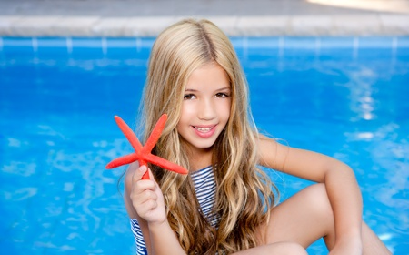 children  girl in summer vacation  pool with starfish photo