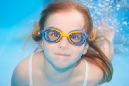 children girl swimming underwater with goggles and funny gesture