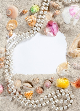 frame composition over beach sand beach with blank paper with pearls and shells photo
