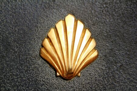 Saint James way shell golden metal on streets soil stone floor photo