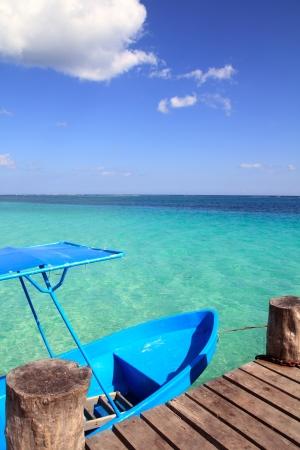 cancun: blue boat in wooden tropical pier in Caribbean beach