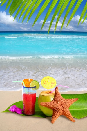 Coconut tropical cocktail with starfish on a Caribbean white sand beach Stock Photo
