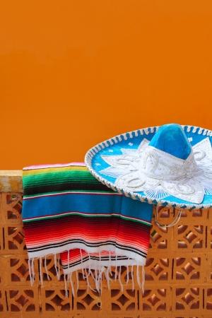 traje mexicano: mariachi charro azul sombrero mexicano y el poncho poncho de color naranja sobre azulejos de la pared