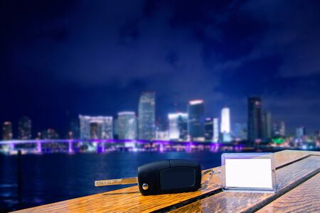 car keys: Car rental keys on wood table with blank paper in Miami night downtown