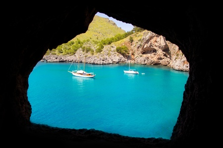 Escorca Sacalobra beach view from cave window with anchor boats in Mallorca photo
