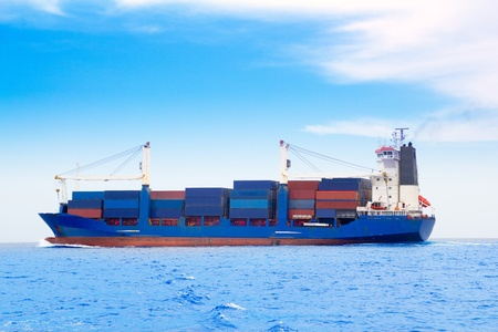 cargo ship with containers in dep blue ocean sea photo