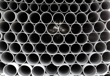 gray PVC tubes plastic pipes stacked in rows pattern photo