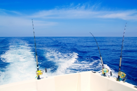 atún: barco de pesca trolling en mar azul profundo con cañas y carretes
