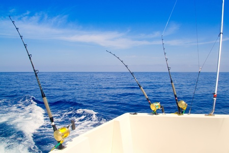 boat fishing trolling in deep blue sea with rods and reels photo