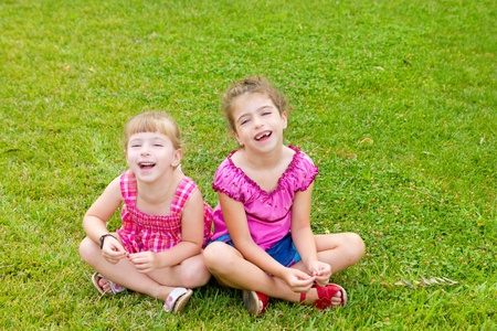 dido: children girls laughing sitting on green grass park
