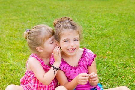 dido: children girl sister friends whispering ear in green grass park