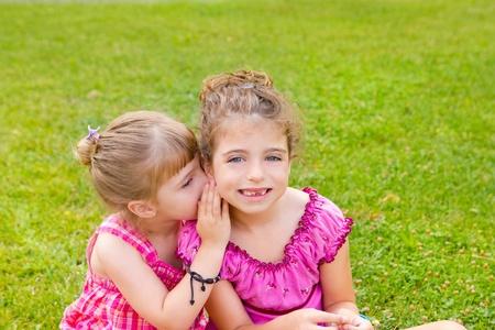 kids hugging: children girl sister friends whispering ear in green grass park