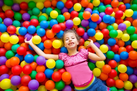 child girl playing on colorful balls playground high view photo