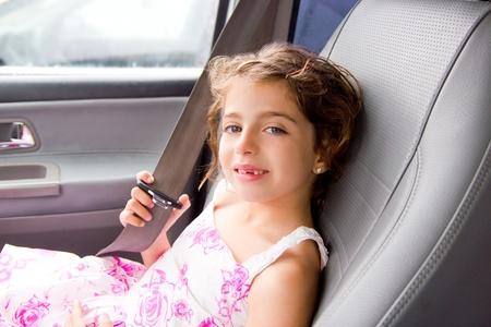 cinturon seguridad: niño coche interiores niña poniendo sonriente de cinturón de seguridad Foto de archivo