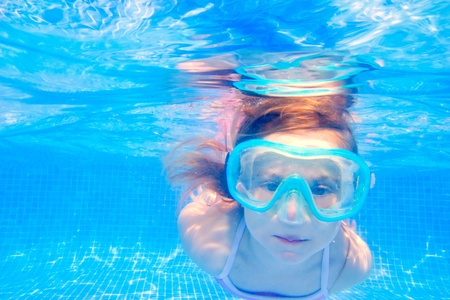 swimming goggles: blond child girl underwater swimming in blue tiles pool