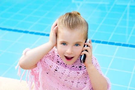 child little girl talking mobile phone in pool with happy gesture photo