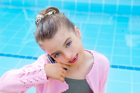 child little indented girl talking mobile phone in swimming pool photo