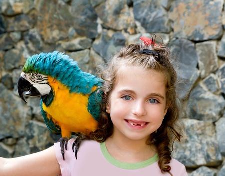 loro: chica de niño de ojos azules con loro amarillo en su hombro Foto de archivo