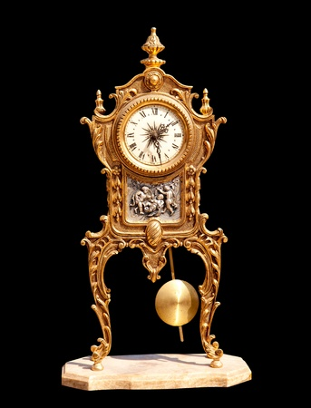 ancient vintage brass pendulum clock isolated on black photo