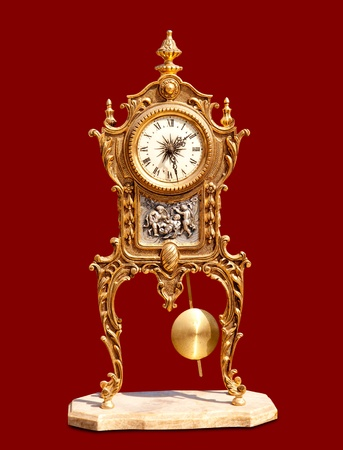 grandfather clock: ancient vintage brass pendulum clock isolated on red Stock Photo