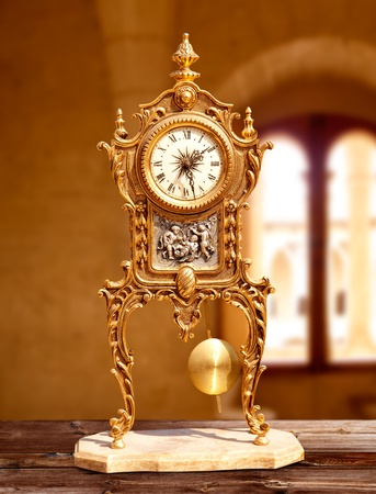 ancient vintage brass pendulum clock in old house interior photo