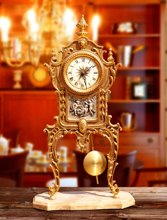 ancient vintage brass pendulum clock in classic indoor photo