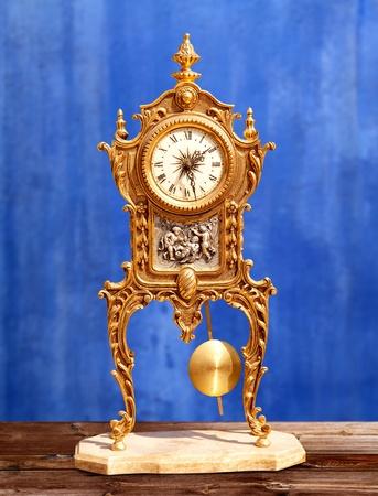 reloj de pendulo: la antigua época de latón dorado reloj de péndulo en fondo del grunge azul Foto de archivo