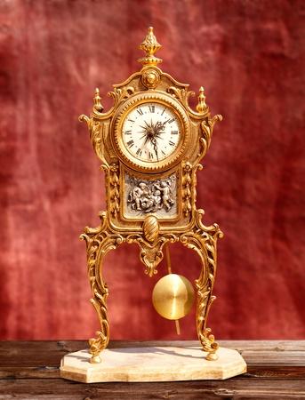 reloj de pendulo: la antigua �poca de lat�n dorado reloj de p�ndulo en el fondo rojo del grunge